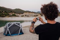 Hipster travel man makes photo of tent stock photos