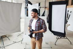 Creative Photographer at Work. Portrait of smiling bearded photographer wearing checked shirt and baseball cap looking away while taking short break from work stock images