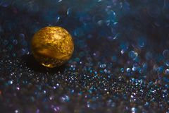 Murano glass golden bead at the dark shiny background royalty free stock photos