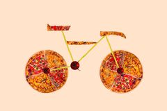 Creative picture of road bicycle made of international pizza and vegetables on white background. Delivery. Royalty Free Stock Photos