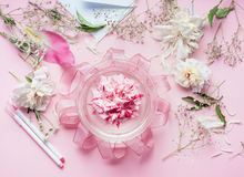 Creative Pink Florist workspace. Pretty floral decoration arrangement with pink roses and plant leaves in glass vase with water an Royalty Free Stock Photography