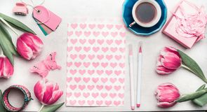 Creative pink mock up with tulips, paper package with hearts, marker pen, tags and cup of coffee on desktop, top view, frame. Layout of spring greeting card Royalty Free Stock Image