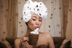 Creative portrait of beautiful funny woman. With cup and dress in coffee beans stock photo