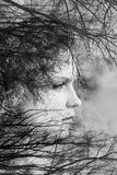 Creative portrait of beautiful young woman made from double exposure effect using photo of trees and nature. Black and white toned royalty free stock image