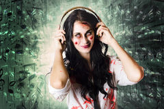 Gothic rock music girl wearing headphones. Creative portrait of a scary goth rock girl listening to heavy metal music though earphone, on music notes background Stock Images