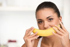 Creative portrait of woman holding yellow banana in her hand. Stock Photos