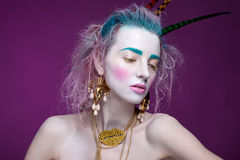 Creative portrait of young woman with artistic make-up. With bright colors in her hair and a white face. stock photography