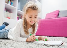 Creative Preschool Child Drawing. Creative Preschool Child, little girl drawing on paper, lying on floor at home royalty free stock photography
