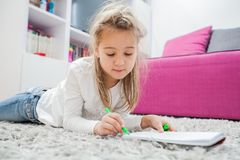 Creative Preschool Child Drawing. Creative Preschool Child, little girl drawing on paper, lying on floor at home stock photo