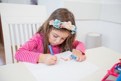 Creative Preschool Child Drawing. Creative Preschool Child, little girl drawing on paper,sitting at table at home stock photo