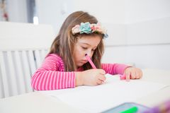 Creative Preschool Child Drawing. Creative Preschool Child, little girl drawing on paper,sitting at table at home stock image