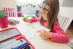 Creative Preschool Child Drawing. Creative Preschool Child, little girl drawing on paper,sitting at table at home royalty free stock photos