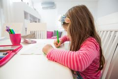Creative Preschool Child Drawing. Creative Preschool Child, little girl drawing on paper,sitting at table at home royalty free stock photo