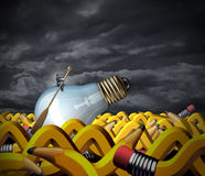 Creative Problem Solving. And business management concept as a businessman sitting on a light bulb with a boat paddle navigating on an ocean made of pencils Stock Images