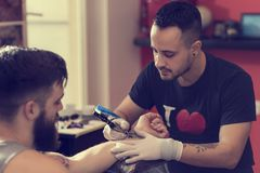 Creative process. Male tattoo artist holding a tattoo gun, showing a process of making tattoos on a male tattooed model's arm royalty free stock image