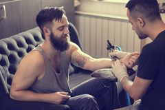 Creative process. Male tattoo artist holding a tattoo gun, showing a process of making tattoos on a male tattooed model's arm stock images