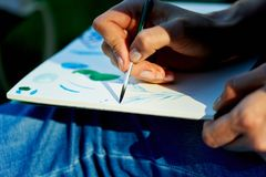 The creative process of watercolor painting.Thin brush touches the canvas Royalty Free Stock Photos