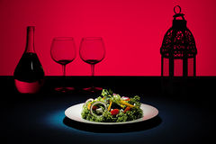 Creative Red Salad. Salad plate with red background and glasses in silhouette Royalty Free Stock Image