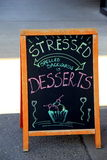 Creative restaurant sign, inviting people in for dessert. Large blackboard sign outside restaurant, inviting people in to enjoy dessert Stock Photography