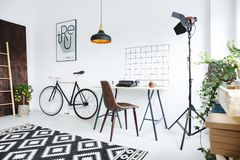 Creative room interior. Creative modern room interior with bike, desk, typewriter and lamp Royalty Free Stock Photo