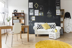 Creative room with vintage furniture. Creative living room with chalkboard wall, wooden desk and vintage furniture Stock Photos