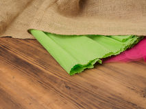 Creative, rustic background. The composition of burlap, crinkled green paper and a red grid on a brown background from. Old wood, rural table. Mock-up for your Stock Image