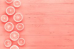 Coral toned oranges pattern. Creative scandinavian style flat lay top view of fresh orange fruit slices on coral wooden table background with copy space. Minimal stock images