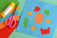 Creative sea animal crafts for kids. Paper ocean creatures, simple fun applique. Kids workshops. Creativity lesson. Scissors, glue stick, pieces of colored royalty free stock images