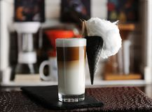 Creative serving latte coffee with cotton candy in waffle cone attached with pin to glass. Brew bar on the background. Creative serving of latte coffee with stock image