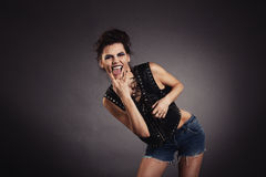 Creative sexy girl showing gesture. Creative sexy girl in black vest standing and showing gesture, rock style Royalty Free Stock Images