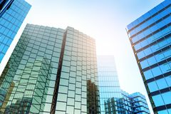 Creative shiny glass buildings. On bright sky background. Urban and corporate concept. 3D Rendering stock illustration