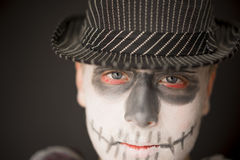 Creative skull makeup for Halloween. Close up of the face of a serious young man wearing creative skull makeup for Halloween dressed in a dark hat and cloak royalty free stock photos