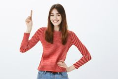 Creative smart girl has one excellent idea. Studio shot of confident good-looking european woman in casual outfit. Holding hand on hip, raising index finger stock photography