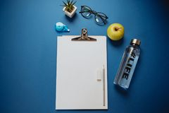 Creative Space for work: a sheet of paper, pencils, phone, glass. Es, headphones on a blue background royalty free stock image
