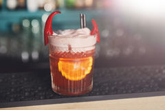 Creative spicy cocktail in night club bar background. Closeup of frothy exotic spicy alcohol cocktail with chili peppers and orange in restaurant at bar Royalty Free Stock Images