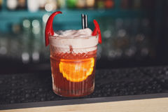 Creative spicy cocktail in night club bar background. Closeup of frothy exotic spicy alcohol cocktail with chili peppers and orange in restaurant at bar Stock Photos