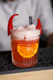 Creative spicy cocktail in night club bar background. Closeup of frothy exotic spicy alcohol cocktail with chili peppers and orange in restaurant at bar Royalty Free Stock Image