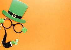 Creative st Patricks Day orange background. Flat lay composition of Irish holiday celebration with photo booth decor: hat, glasses royalty free stock images