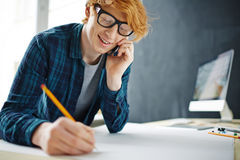Creative Student Calling by Smartphone while Drawing Stock Photography