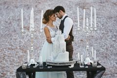 Creative and stylish wedding cake on the wooden table in front of the fashionable and beautiful couple of sweethearts stock photos