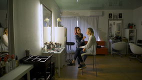 Creative Stylist makes image for his client. Picture of working day inside the beauty- sit on chair client beautiful young woman. Make-up artist doing make-up stock footage