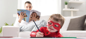 Creative superhero. Cute superhero boy drawing with mother reading on background Stock Images