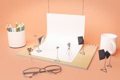 Creative supplies photo studio. Creative tiny photo studio made out of supplies: white paper, coffee cup, pencils, glasses and other items on peachy background Royalty Free Stock Images
