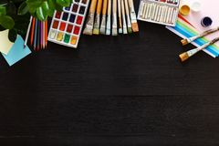 Creative art painting drawing supplies tools set on wooden desk top view. Creative supplies set on desk top view, tools for school creative work on black wooden stock image