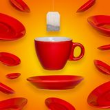 Creative surreal design with a red coffee cup and saucer and tea bag. On a yellow background. A cup and saucers flying in the air royalty free stock photography