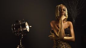 Creative surreal portrait of african american female model with glossy golden makeup and headwear posing to the. Camera. Bronze bodypaint, black studio stock video