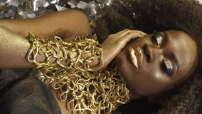 Creative surreal portrait of african american female model with gold glossy makeup Face art. Silver glossy confetti