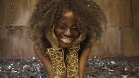 Creative surreal portrait of african american female model with gold glossy makeup surrounded by silver confetti. Close-up portrait of african american female stock footage