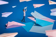 Creative surrealism design with origami paper planes. Young girl let paper airplanes. Stock Image