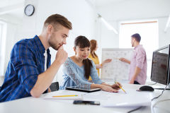 Creative team with blueprint at office Stock Photography